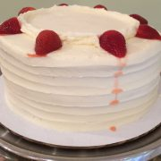Vanilla frosting with strawberries added between the layers and on the top of the cake.