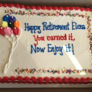 This 1/2 sheet cake has an icing drawing of multi color ballons and 9 word inscription.