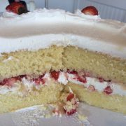 Yellow cake with fresh strawberries added between layers and on top.