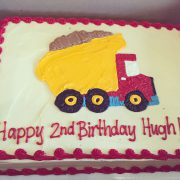 This 1/4 sheet cake has an icing drawing of a dump truck and a 4 word inscription.