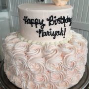 This cake has base color change to both tiers and rosettes on the bottom tier.  The top tier has a hard sugar flower.
