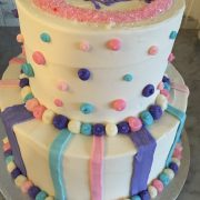 This cake has thick stripes on the bottom tier and polka dots on the top tier.